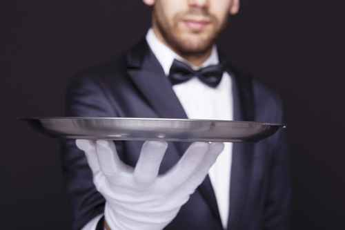Close-up of a waiter holding an empty silver tray against dark b